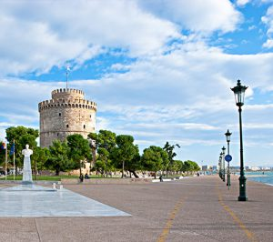Thessaloniki, Greece - October 17, 2013: The White Tower and Admiral Votsis Statue locates on the sea promenade, the favourite place for tourist walks.